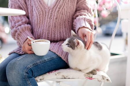 Young woman is drinking coffee and stroking pet cat in spring garden. Girl is sitting outdoors in cafe on blooming city streets with pink magnolia flowers.
