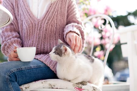 Young woman is drinking coffee with cute cat in spring cafe on city streets. Girl is sitting outdoors in blooming garden with pink magnolia flowers.