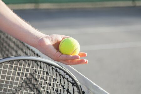 Sportsman is playing tennis on court outdoor. Male hand holds tennis racket and gives yellow ball over net. Man has workout. Sports activities in summer.
