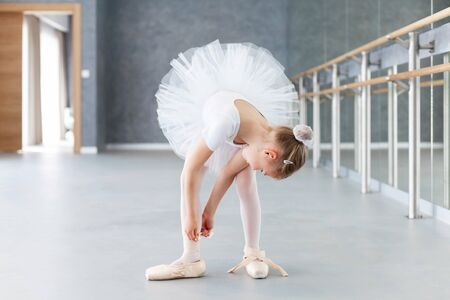 Funny little ballerina is trying on big pointe shoes in ballet class. Cute child girl is dancer. Kid is wearing in white ballet clothes and dancing dress with tutu skirt. 写真素材