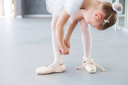 Funny little ballerina is trying on big adult pointe shoes in ballet class. Cute child girl is dancer. Kid is wearing in white ballet clothes and dancing dress with tutu skirt.