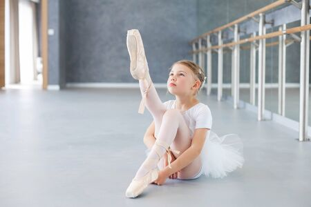 Little ballerina is trying on pointe shoes in ballet class. Cute child girl is sitting on floor under barre. Kid is wearing in white ballet clothes and dancing dress with tutu skirt.