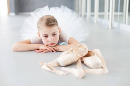 Little ballerina is looking at pointe shoes in ballet class. Cute child girl is dreaming and lying on floor. Tired kid is wearing white dress with tutu skirt after dance training.