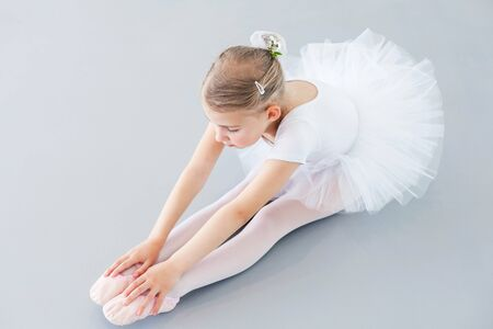 Cute little ballerina is doing stretching exercises on light background. Child girl is studying in ballet classical school. Kid is wearing in white ballet clothes and dancing dress with tutu skirt.