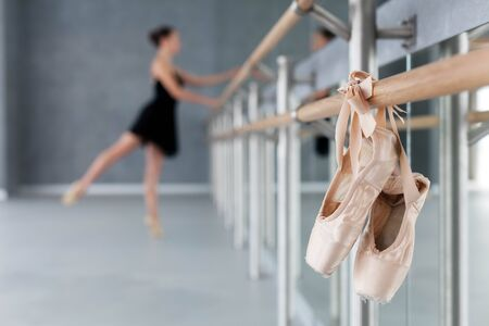 Pointe shoes hang on ballet barre. Ballerina has dance training in class room. Girl is doing exercises in front of mirror. Blurred background. 写真素材