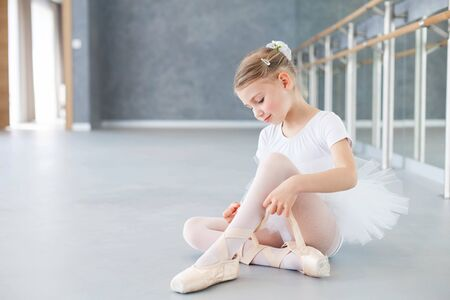Little ballerina is trying on pointe shoes in ballet class. Cute kid girl is sitting on floor under barre. Child is wearing in white ballet clothes and dancing dress with tutu skirt.
