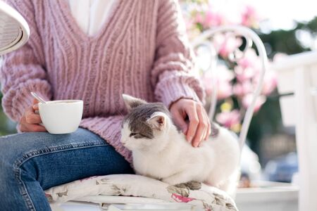 Young woman is drinking coffee and stroking cute cat in spring cafe on city streets. Girl is sitting outdoors in blooming garden with pink magnolia flowers.