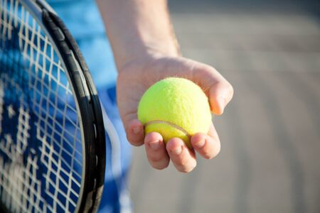 Sportsman is playing tennis on court outdoor. Male hand holds tennis racket and gives yellow ball. Man has workout. Sports activities in summer. 写真素材