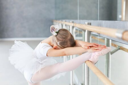 Little ballerina is studying in ballet classical school. Cute child girl is doing stretching exercises with leg on barre. Kid is wearing in white ballet clothes and dancing dress with tutu skirt. 写真素材