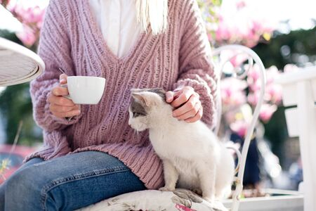 Young woman is drinking coffee and stroking cat in spring cafe on city streets. Girl is sitting outdoors in blooming garden with pink magnolia flowers.