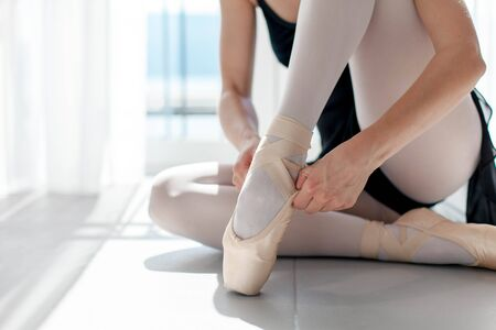 Ballerina puts on ballet pointe shoes. Girl is sitting on floor in sunny dance class room. Close up.