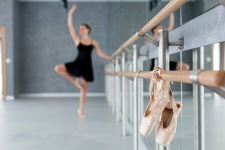 Pointe shoes hang on ballet barre. Blurred background with dancing ballerina. Girl has workout in ballet classic school.
