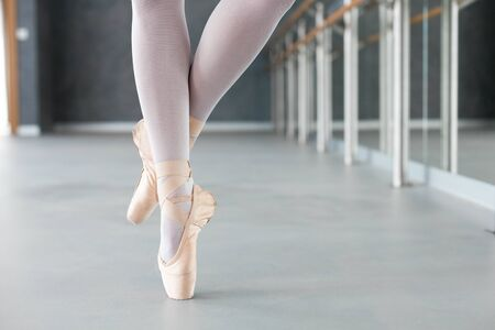 Ballerinas legs in ballet pointe shoes. Close up. Girl is dancing. Dancer has workout in ballet school.