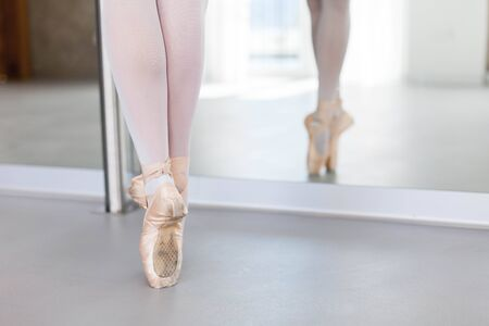 Ballerinas legs in ballet pointe shoes. Close up. Girl is standing. Dancer has workout in ballet school. Stock Photo
