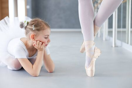 Little ballerina is looking at legs of professional ballet dancer in pointe shoes. Cute kid girl dreaming. Concept of classical dance school, practicing for children.