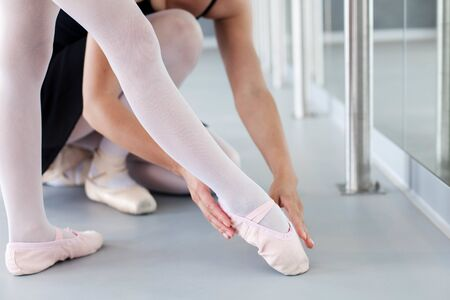 Little ballerina and ballet teacher in classical dancing school. Female dance trainer corrects kids leg in ballet shoes in choreographic position. Practicing for children. Close up.