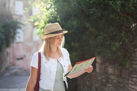 Woman traveler looks at city map at town street in Provence, France. Girl tourist is searching apartment, housing. Concept of student travel, summer vacation, female tourism, adventure, trip.