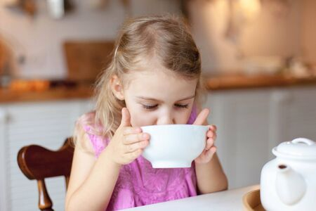 Child girl drinks tea at kitchen table. Breakfast with teapot, mug. Cozy home atmosphere.