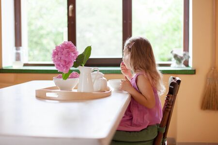 Kid girl drinks tea at kitchen table. Child gourmet is tasting sweets. Spring breakfast with teapot, mug, hydrangea flowers. Cozy home atmosphere. 免版税图像