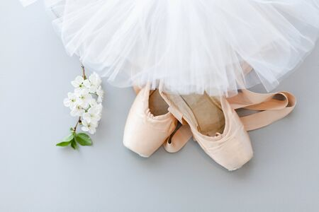 Ballet pointe shoes and white tutu skirt on gray background with blooming cherry flowers. Concept of dance, spring, ballet school, ballerinas clothes, stuff and things. Top view, flat lay.