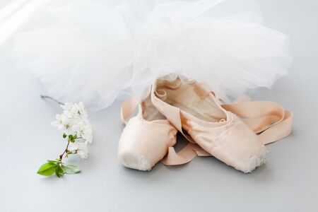 Ballet pointe shoes and white tutu skirt on gray background with blooming sakura flowers. Concept of dance, spring, ballet school, ballerinas clothes, stuff and things. 免版税图像