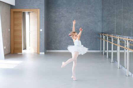 Little ballerina is dancing in ballet class. Cute child girl is wearing in white ballet shoes, clothes and dress with tutu skirt. Kid in classical dance school for children.