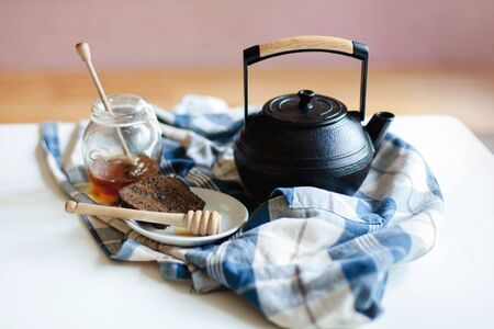 Kitchen still life about tea time. Black cast iron teapot, jar of honey with honey spoon and rye bread are serving on plaid towel on table. Cozy home authentic atmosphere. 免版税图像