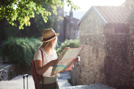 Girl traveler is using city map at town street in Europe. Woman tourist is searching apartment, house. Concept of travel, summer vacation, solo female tourism, adventure, trip, journey