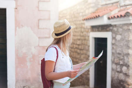 Woman traveler in hat with map and backpack at old town streets. Concept of student travel, summer vacation, female tourism, adventure, trip, journey. Girl tourist is searching apartment, housing.