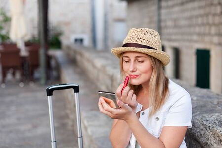 Woman traveler corrects makeup and applies red lipstick outside. Concept of student travel, summer vacation, female tourism, trip, adventure.
