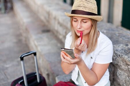 Girl traveler corrects makeup and applies red lipstick outside. Woman tourist with luggage sits at town street in Europe. Concept of student travel, summer vacation, female tourism, trip, adventure.