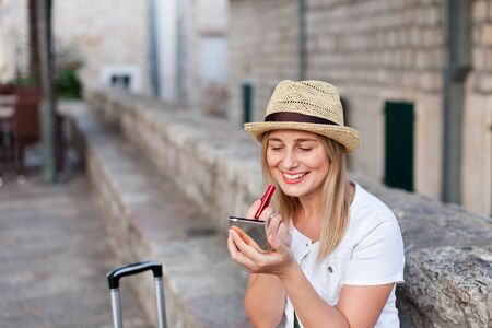Happy woman traveler corrects makeup with red lipstick outside. Girl tourist with luggage is smiling at town street in Europe. Concept of travel, summer vacation, female tourism, trip, adventure.