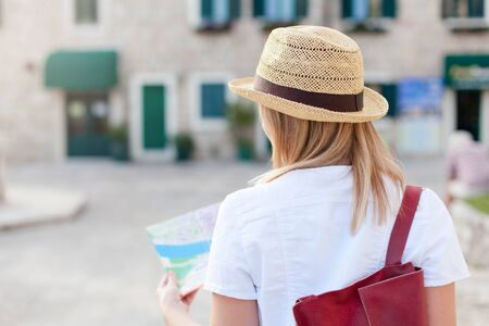 Woman traveler with city map is searching apartment. Girl tourist is exploring locations, walking in old town. Concept of travel, summer vacation, female tourism, adventure.