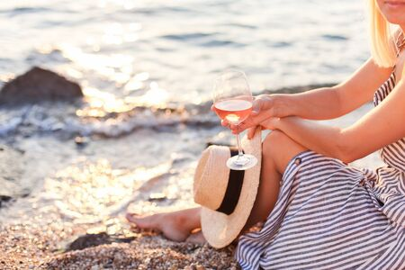 Woman is sitting on sea beach with wineglass of pink wine at sunset in summer vacation in resort. Tourist girl in striped dress with straw hat is enjoying life, relaxing, drinking, traveling. 免版税图像
