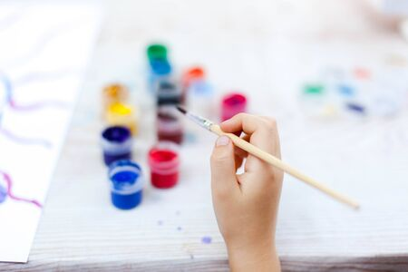 Kid hand with brush. Child is painting. Concept of children leisure, hobby, child artist. Close up. 免版税图像