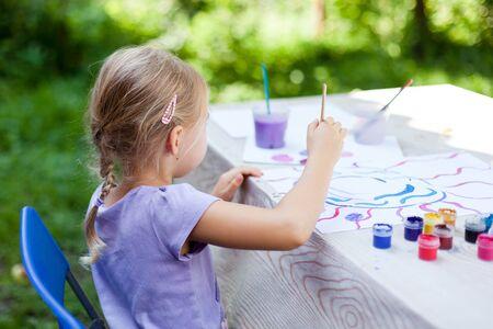Kid is painting in garden. Children leisure in summer holidays.