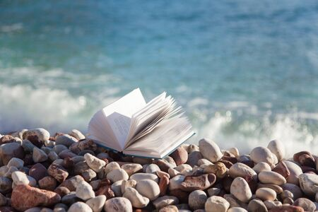 Book on sea beach. Concept of reading paper book, relaxation, enjoying summer vacation.