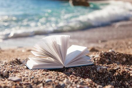 Open book on sea beach. Concept of reading, relaxation on coast, enjoying summer holidays. 免版税图像
