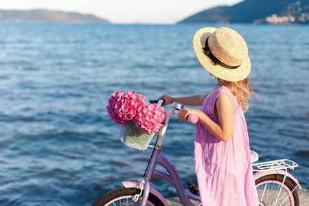 Little lady with bicycle and pink flowers on sea beach. Kid girl in straw hat and dress is riding on coastline. Hydrangea is in bike basket. Concept of tenderness, childhood, romantic summer.