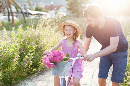 Father is teaching daughter to ride on bicycle. Family summer activities. Happy kid girl has support from daddy. Child smiles and has fun.