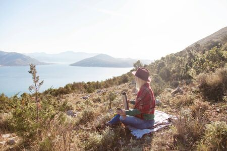 Woman traveler in autumn mountains above sea. Fall picnic with thermos of coffee or tea. Girl in plaid and hat is enjoying amazing view. Concept of traveling and relaxation at nature.