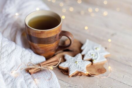 Christmas still life. Mug of tea, gingerbread glazed cookies, cinnamon at wooden background with glares. Cozy tea time with homemade sweets and cup of hot beverage. Winter food, drink, new year lights