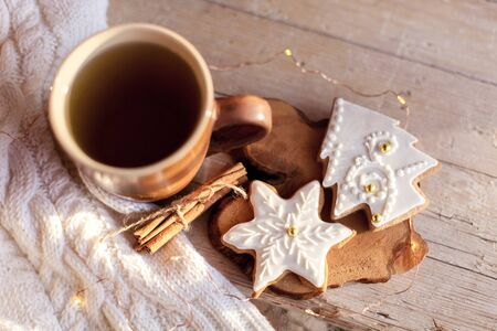 Mug of tea, Christmas gingerbread glazed cookies, cinnamon at wooden background with glares. Cozy tea time with homemade sweets and cup of hot beverage. Winter food, drink, new year lights