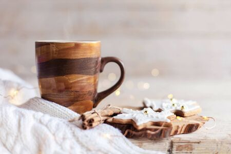 Christmas still life. Mug of hot steamy coffee, gingerbread cookies at wooden background with glares. Cozy morning breakfast with homemade sweets and cup of tea or cocoa. Winter drink, new year lights
