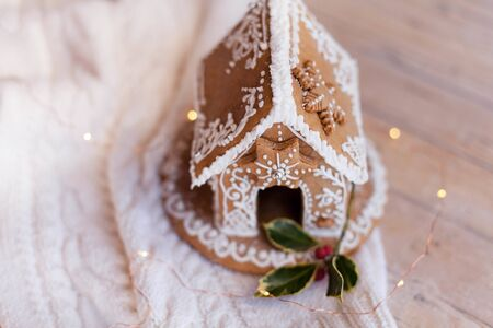 Gingerbread house, Christmas cozy decorations on wooden and knitted background with glares. Handmade sweets is decorated with holly and cute white ornaments, new year lights, garland.