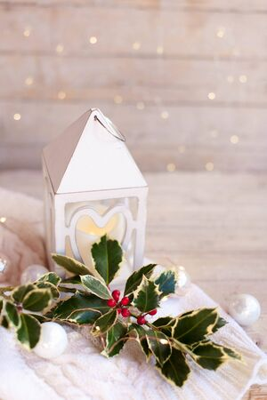 Christmas decorations. White night light and holly branch on wooden background with glares. Cozy winter still life.