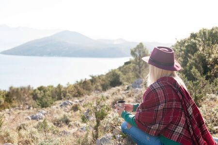 Woman traveler in mountains looks at autumn sea. Cozy fall picnic with coffee on coast. Girl in warm plaid and hat drinks hot tea from mug. Enjoying life, relaxation at nature, traveling concept.