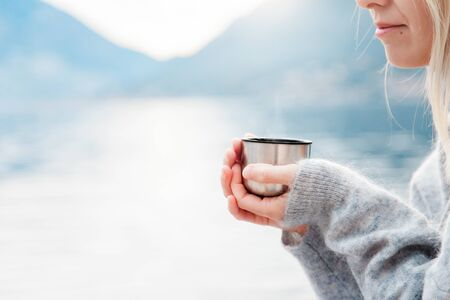 Woman with mug of hot steamy beverage by winter sea, blue mountains. Cozy picnic with of tea, coffee or cocoa on beach. Girl is enjoying nature, life, relaxation, Christmas mood.