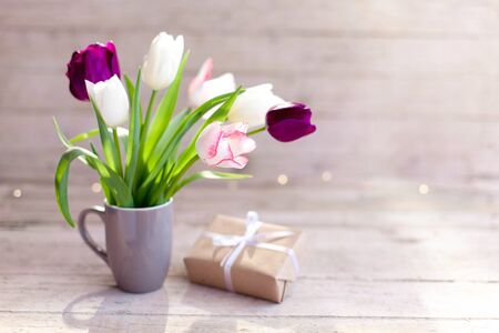 Spring flowers and gift box at wooden background. Blooming tulips in gray cup. Pink, white, lilac and purple bouquet in vase. Cozy still life. Copy space. 免版税图像