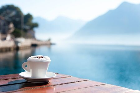 Cup of coffee on wooden table at sea beach. Authentic countryside cafe in rustic style. Morning breakfast with amazing view of winter lake and blue mountains. Cozy sunny still life. Copy space.